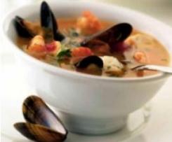Sopa de pescado acompañada de buñuelos de gambas y confitura de pimientos rojos.